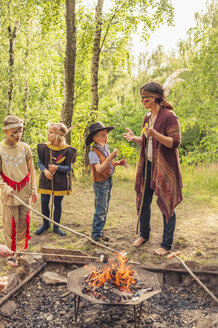 Germany, Saxony, Indians and cowboy party, Children rasting marshmallows on sticks - MJF001660