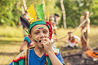 Germany, Saxony, Indians and cowboy party, Boy eating roasted marshmallow - MJF001661
