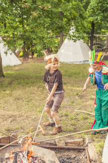 Germany, Saxony, Indians and cowboy party, Children rasting marshmallows on sticks - MJF001667