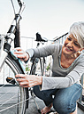 Mature woman cleaning her city bike with a cloth on balcony - MFF001816