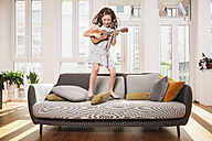Happy girl playing mini guitar while jumping on a couch in living room at home - MFF001692