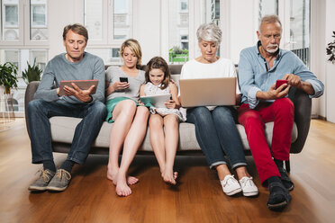 Group picture of three generations family sitting on one couch using different digital devices - MFF001696