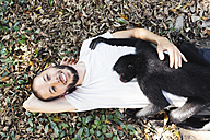 Bolivia, Coroico, portrait of smiling man laying on the ground with black spider monkey on his chest - GEMF000261