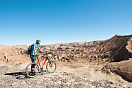 Chile, Man holding a mountain bike and looking to the Death Valley in the Atacama Desert - GEMF000259