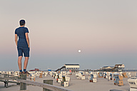 Germany, St Peter-Ording, young man standing on wooden fence looking at the beach - MEMF000817