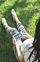 Pregnant woman sitting in the garden with smartphone - DEGF000460