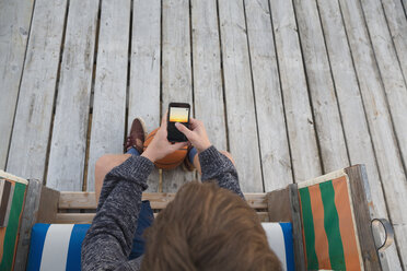 Teenage boy with basketball and smartphone sitting in hooded beach chair - MEMF000833