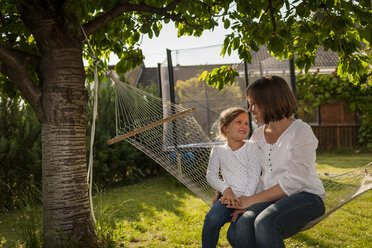 Mother and her little daughter sitting on a hammock in the garden - PAF001448
