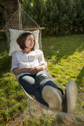 Woman relaxing on a hammock in the garden - PAF001453