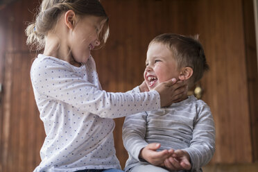 Brother and sister laughing together - PAF001455