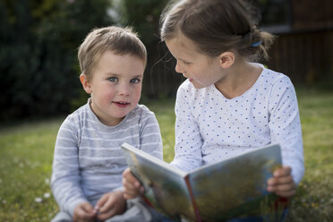 Girl and her little brother sitting on a meadow with a picture book - PAF001459