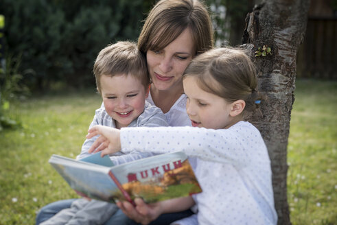 Mother and her two children sitting on a meadow reading a picture book - PAF001464