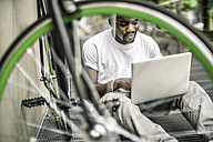 Portrait of young man with bicycleand laptop - RIBF000118