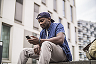 Germany, Cologne, young man with smartphone - RIBF000126