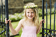 Portrait of smiling girl with tooth gap wearing floral wreath - GDF000764
