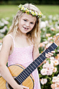 Portrait of smiling little girl with guitar wearing floral wreath - GDF000769
