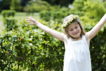 Portrait of smiling girl with closed eyes and outstretched arms wearing floral wreath - GDF000774