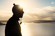 Peru, silhouette of man with cap in front of Lake Titicaca at sunset - GEMF000266