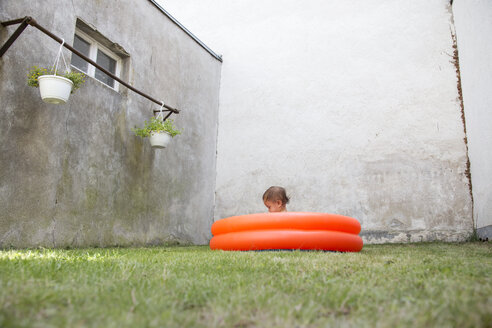 Germany, Freiburg, little girl sitting in a paddling pool at backyard - DR001677
