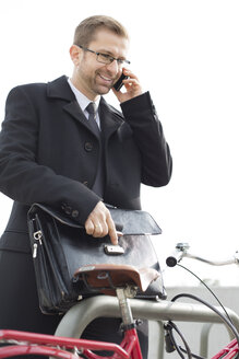 Businessman outdoors with briefcase and bicycle on the phone - WESTF021284