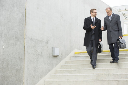 Two businessmen walking and talking on stairs - WESTF021316