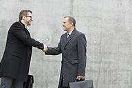 Two businessmen shaking hands at concrete wall - WESTF021318