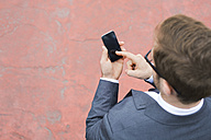 Businessman outdoors using cell phone - WESTF021370