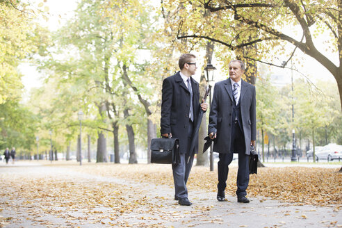 Two businessmen walking and talking in park - WESTF021376