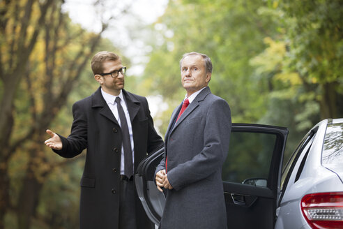 Chauffeur opening car door for businessman getting out - WESTF021353