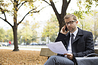 Businessman on park bench looking at document talking on phone - WESTF021360
