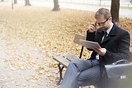 Businessman on park bench using digital tablet - WESTF021380