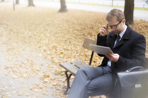 Businessman on park bench using digital tablet - WESTF021380