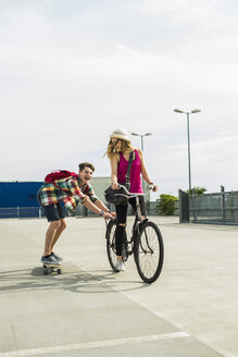 Happy young couple with bicycle and skateboard - UUF004862