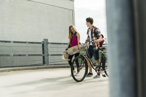 Happy young couple with bicycle and skateboard - UUF004875