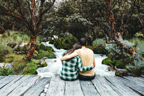 Peru, couple sitting arm in arm on a wooden bridge enjoying nature - GEMF000269