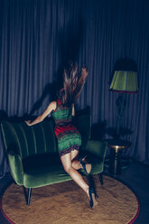 Back view of young woman kneeling on couch tossing her hair - CHAF000533