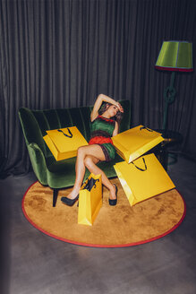 Tired young woman sitting on couch with shopping bags - CHAF000534