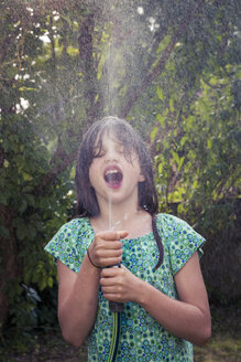 Girl cooling herself with garden hose - LVF003681