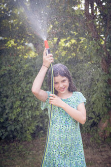 Girl cooling herself with garden hose - LVF003682