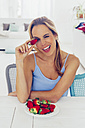 Portrait of blond woman sitting at  table having fun with strawberries - CHAF000408