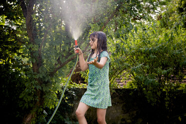 Girl cooling herself with garden hose - LVF003676