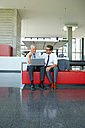 Two smiling businessmen working on laptop in office lobby - CHAF000373