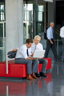 Two businessmen working on laptop in office lobby - CHAF000947
