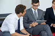 Three business colleagues with digital tablet discussing in office lobby - CHAF000377