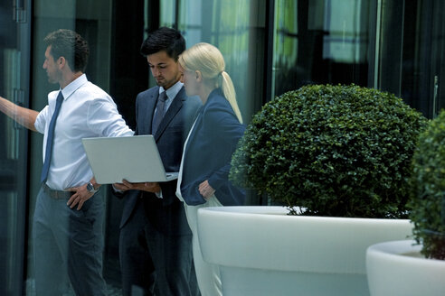Businessman and businesswoman with laptop in an atrium - CHAF000380