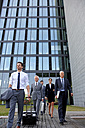 Team of business professionals walking out of office building with luggage - CHAF000383