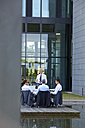 Manager talking to staff sitting on chairs outside office building - CHAF000384