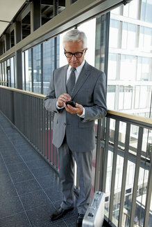 Senior businessman standing on office corridor looking on cell phone - CHAF000390