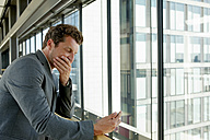Terrified businessman reading text message on cell phone - CHAF000392