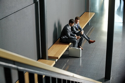 Two young businessmen sitting on bench using cell phone in office lobby - CHAF000395